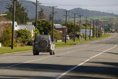 Street with power poles, car, and shadows - stock photo