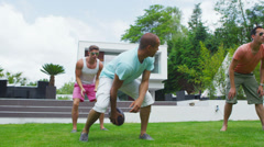 Athletic group of male friends play football in the garden of contemporary home - stock footage