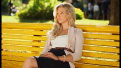 Young beautiful female on date sitting in park waiting boyfriend, click for HD Stock Footage