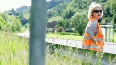 Woman in protective suit waiting for car assistance - stock footage
