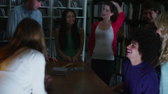 Happy and carefree group of young friends gathered around a piano at a party - stock footage