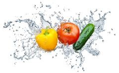 Tomato, cucumber, pepper in spray of water Stock Photos