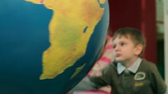 Young boy turning around big Earth globe - stock footage