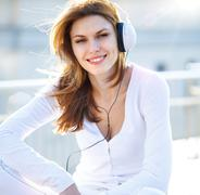Captivating young woman listens to music through headphones Stock Photos