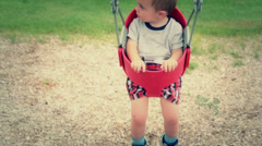 A toddler on a swing at small park Stock Footage
