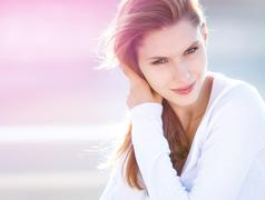 Lively young woman touches her hair - stock photo