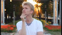 Young blond man crazy idea inspiration, sunny park background , click for HD Stock Footage