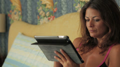 Beautiful businesswoman in lingerie surfs in the internet with her tablet Stock Footage