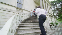 Diverse group of students & teachers using the staircase of university building  Stock Footage