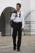 Man in black tie walking the morning after Stock Photos