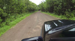 SUV Driving Down Tropical Dirt Road Stock Footage