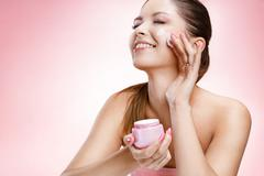 Young beautiful girl with a face cream - stock photo
