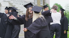 Happy student friends hugging and congratulating each other on graduation day - stock footage