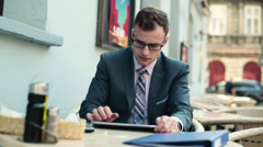 Young businessman with tablet and cellphone in cafe HD Stock Footage