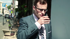 Young businessman drinking coffee in city, steadicam shot HD Stock Footage