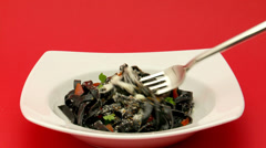 Black pasta,white plate, fork Stock Footage