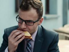 Businessman eating sandwich in cafe, steadicam shot NTSC Stock Footage