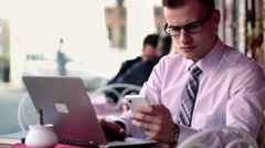 Stock Video Footage of Young businessman with smartphone and laptop sitting in cafe HD