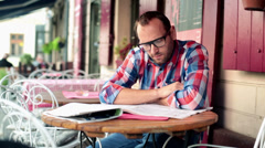 Young man reading newspaper in cafe HD Stock Footage