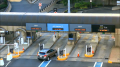 Car pays at toll booth garage exit Stock Footage