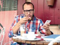 Young man with smartphone during breakfast in cafe NTSC - stock footage