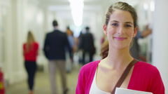 Portrait of a young female caucasian student standing in a busy college hallway Stock Footage