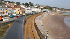 Train travelling away from camera viewed from bridge on railway bordering sand a Stock Footage