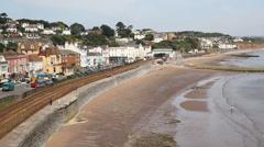 Dawlish Devon England with railway track and sea on blue sky summer day PAN Stock Footage