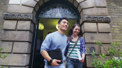 Happy group of students leaving through the doorway of a university building - stock footage