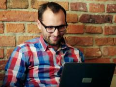Youn man with laptop sitting by the brick wall NTSC Stock Footage