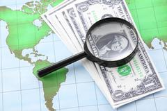 Magnifying glass black frame and currency on world map paper. Stock Photos