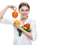 promo girl holding a paprika and cucumbers - isolated on white background - stock photo