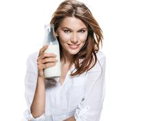 satisfied european woman & bottle of milk - isolated on white background - stock photo