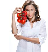 Young beautiful woman with bunch of tomatoes in hand isolated on white - stock photo