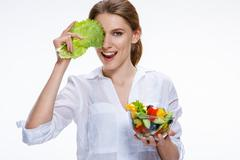 Young beautiful woman with vegetable salad bowl in one hand and cabbage leaf Stock Photos