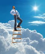 Laughing confident businessman standing at the top of ladder high in the sky - stock illustration