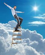 Businessman standing at the ladder high in the sky balancing on top - stock photo