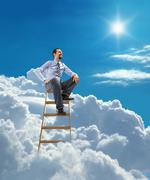 Young confident businessman sits atop at the ladder high in the sky - stock illustration