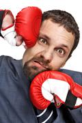 Close-up young businessman struck in the face by hands in boxing gloves Stock Photos