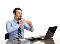 Businessman playing on flute in front of laptop - stock photo