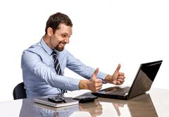 Young modern businessman excited with his success giving thumbs up to the laptop Stock Photos