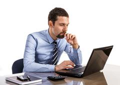 Thoughtful businessman at office desk looking on laptop Stock Photos