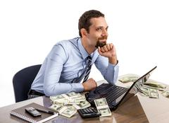Successful smiling businessman with a lot of dollar stacks at the desk Stock Photos