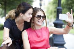 Happy young women taking pictures on your phone Stock Photos