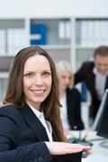 Smiling businesswoman in a busy office Stock Photos
