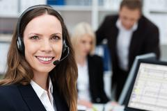 Stock Photo of friendly attractive young call centre operator