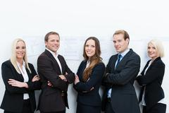 Happy professional team standing with folded arms Stock Photos