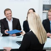 job applicant handing over her curriculum vitae - stock photo