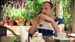 Young man drinking ice coffee in cafe HD Stock Footage