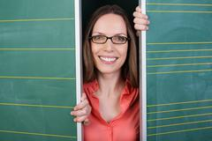 Smiling woman peering between two chalkboards Stock Photos